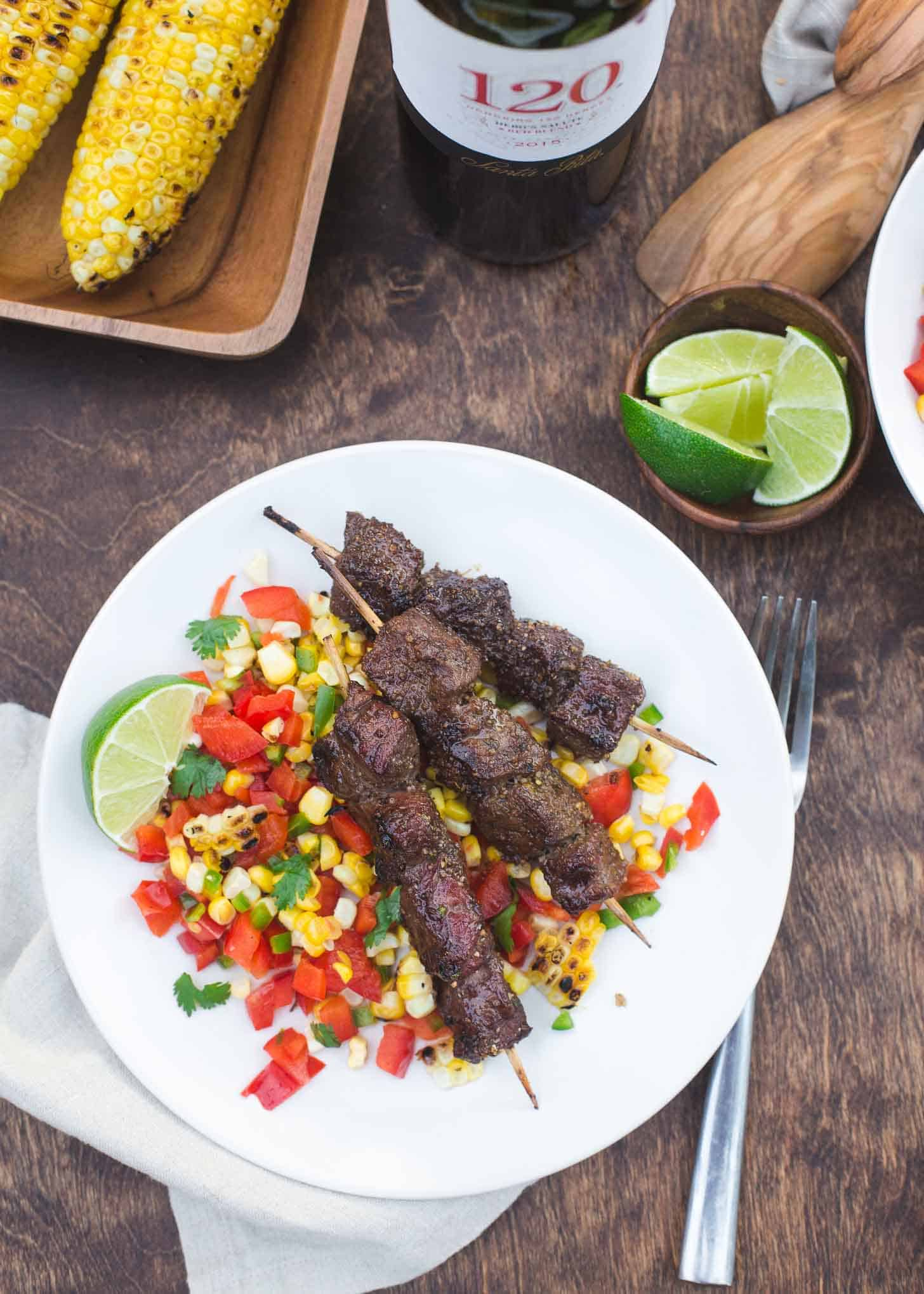 beef skewers over corn salsa on a white plate