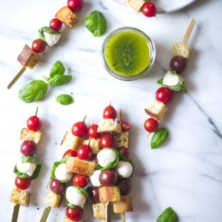 Panzanella Salad Skewers on a white table with basil leaves