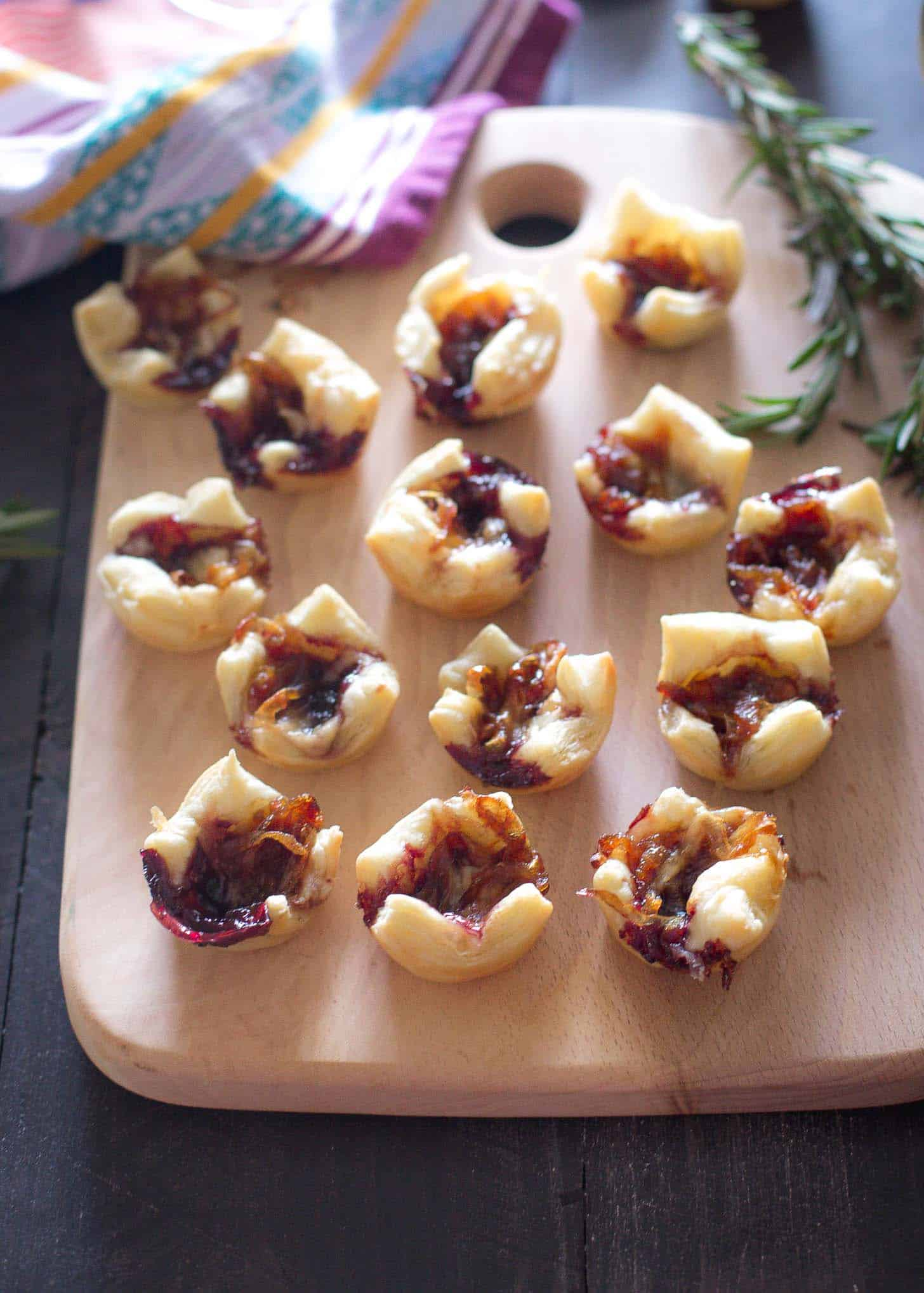 Puff Pastry Bites with Caramelized Onions and Gouda on a wooden tray