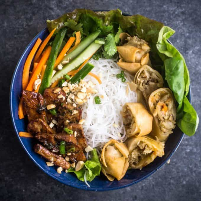 noodle bowls topped with spring rolls
