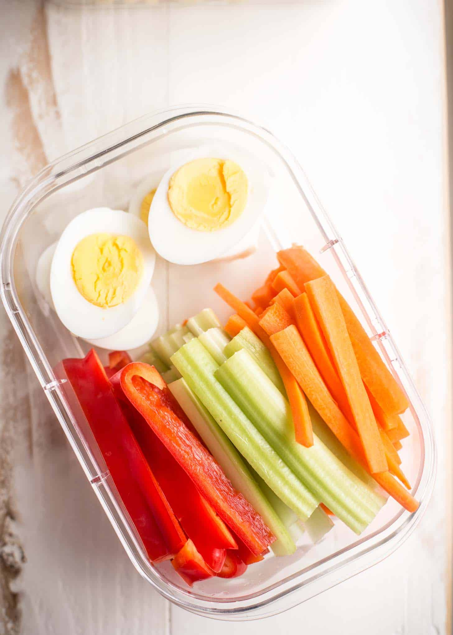 boiled eggs and sliced vegetables in a plastic container