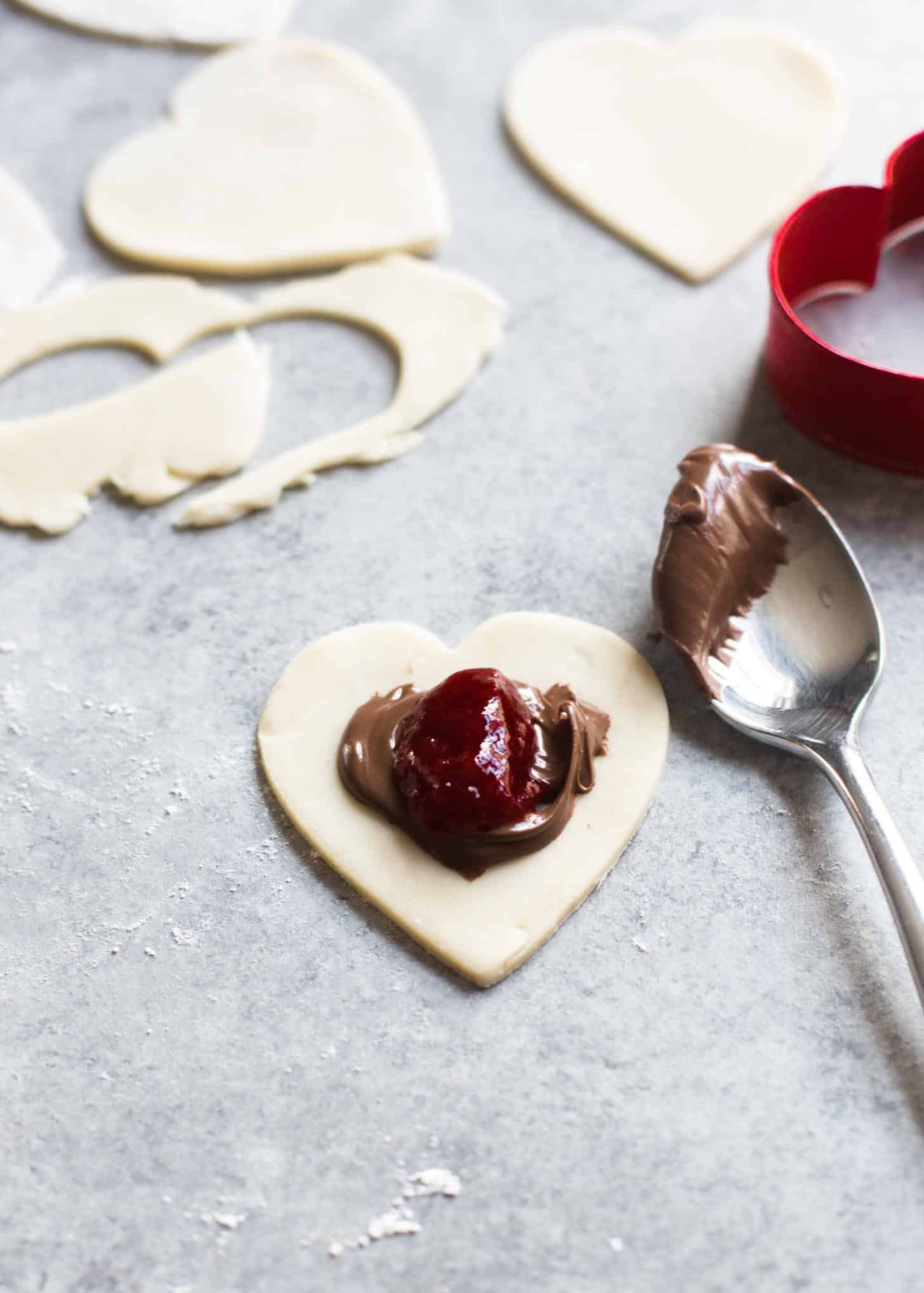 adding strawberry jam and nutella to a heart shaped piece of dough