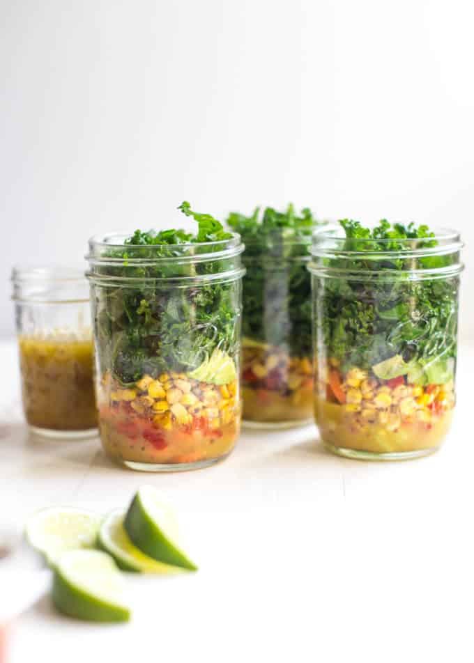 3 mason jar salads on a white table