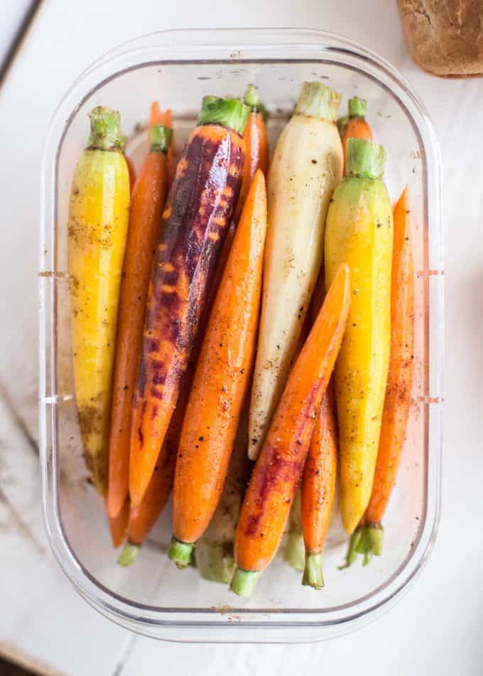cooked carrots in a container on a white table