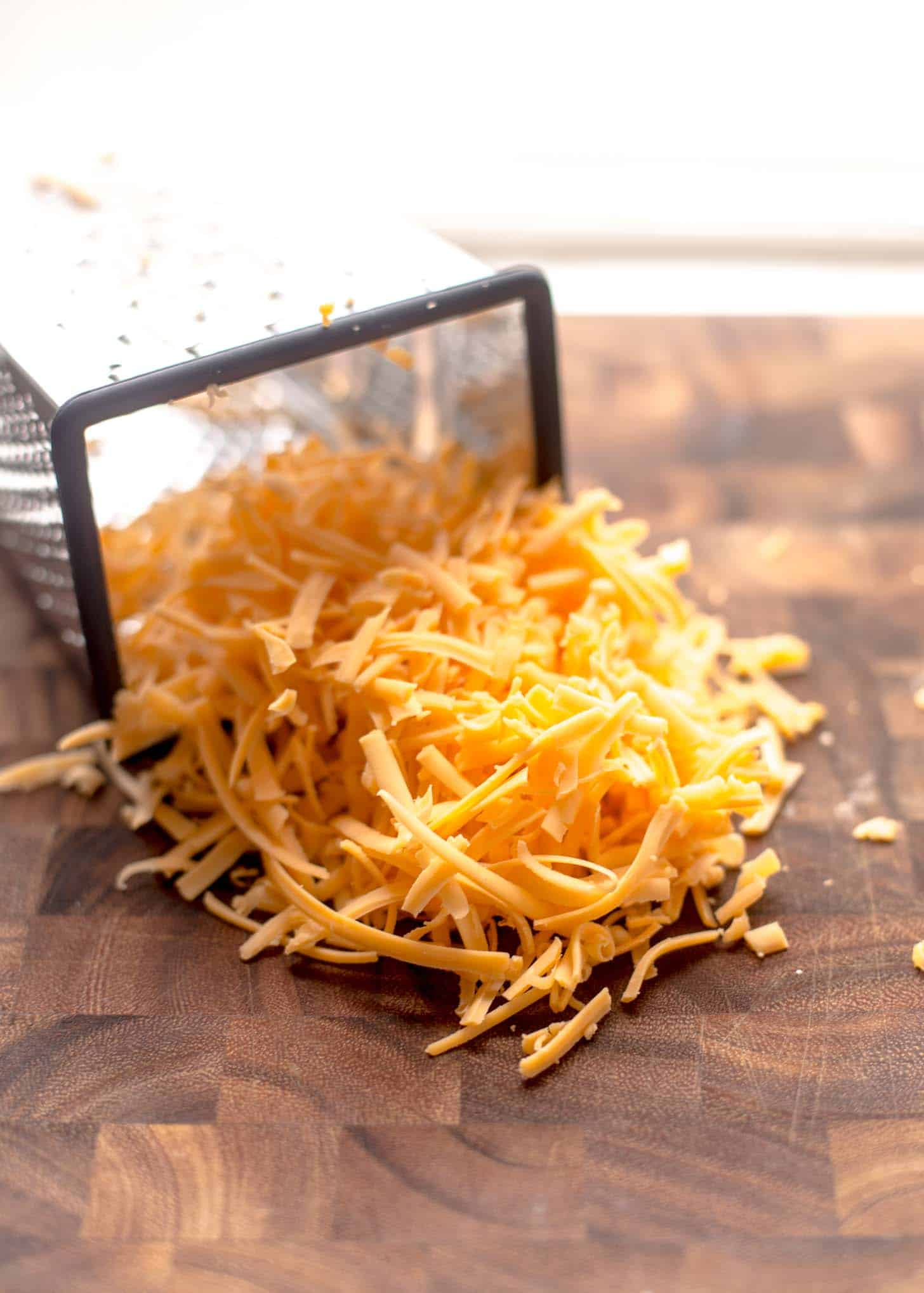 grated cheddar on a wooden butcher block