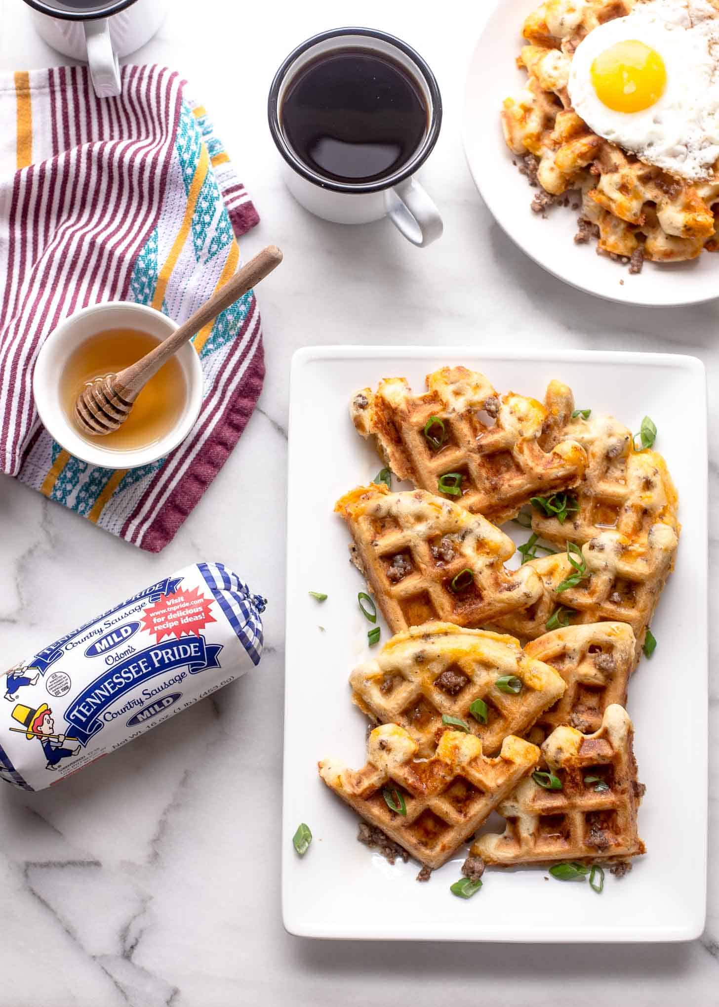 savory waffles, syrup, coffee and sausage on a white table