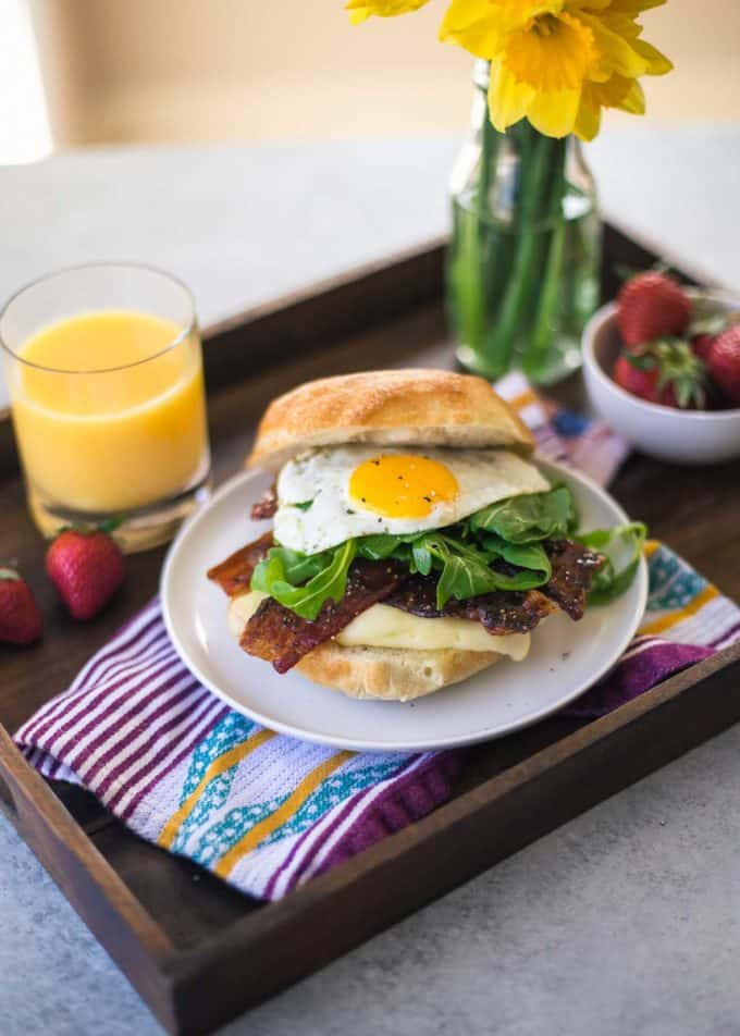 Bacon, Egg, Brie and Arugula Breakfast Sandwich on a wooden tray
