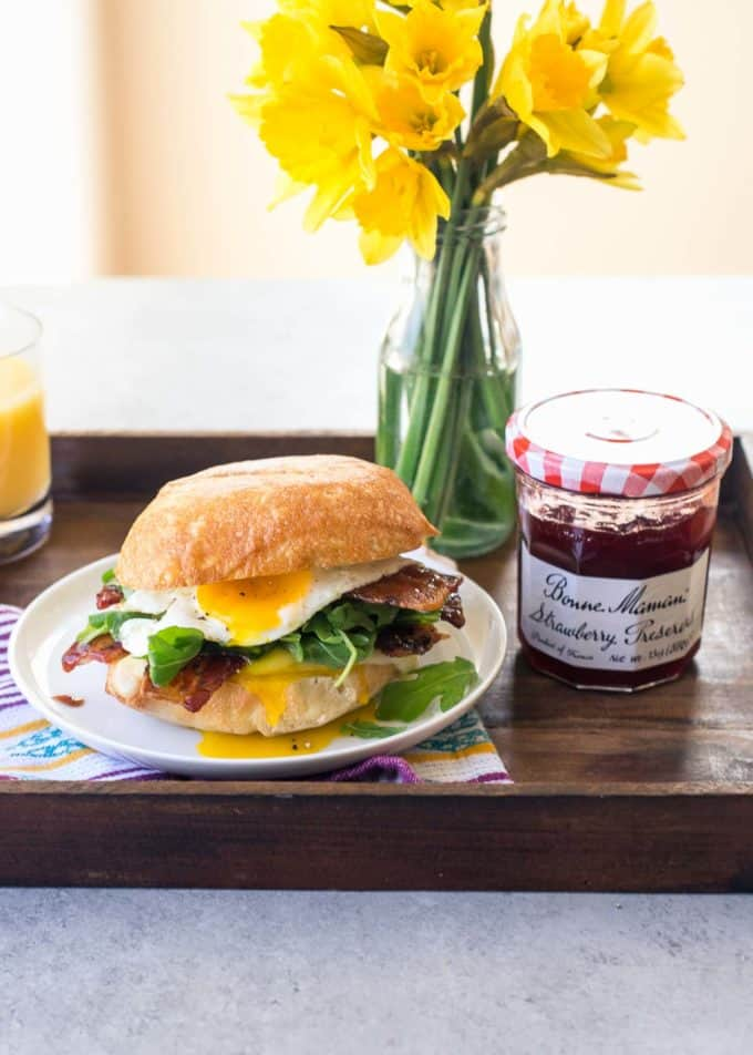 Bacon, Egg, Brie and Arugula Breakfast Sandwich on a tray with strawberry preserves