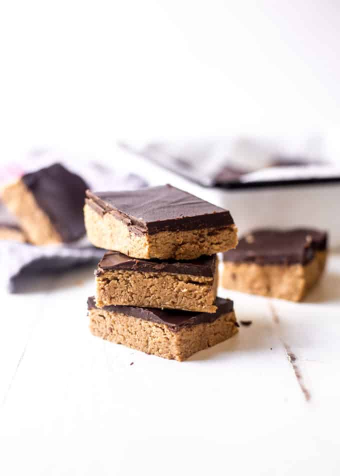 No Bake Chocolate Peanut Butter Bars stacked on a white table