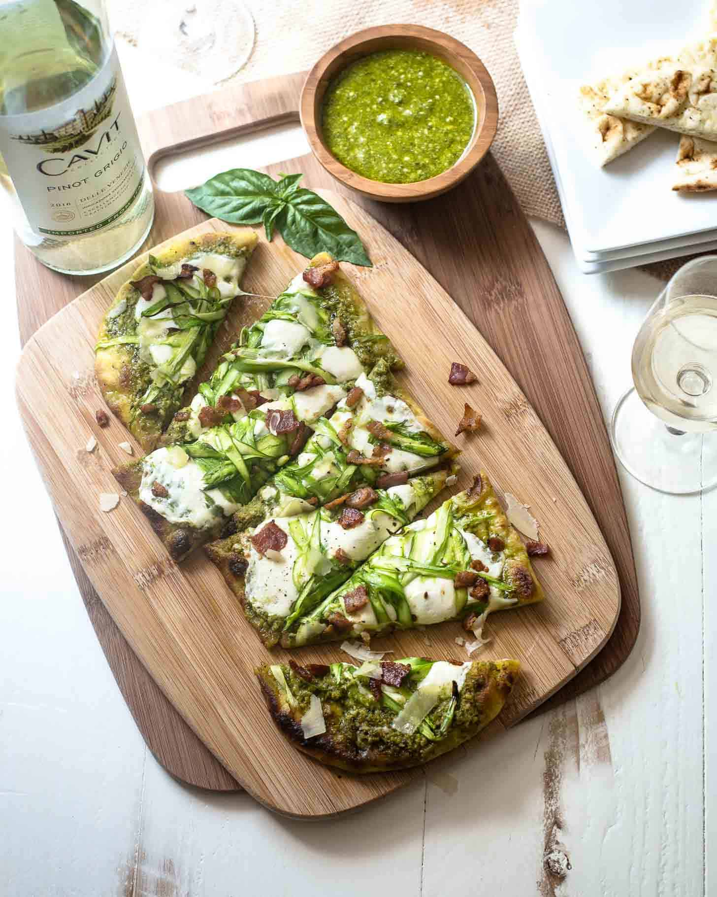 Pesto Flatbread with Shaved Asparagus and Bacon sliced on a wooden cutting board