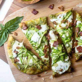 pesto flatbread sliced on a wooden cutting board