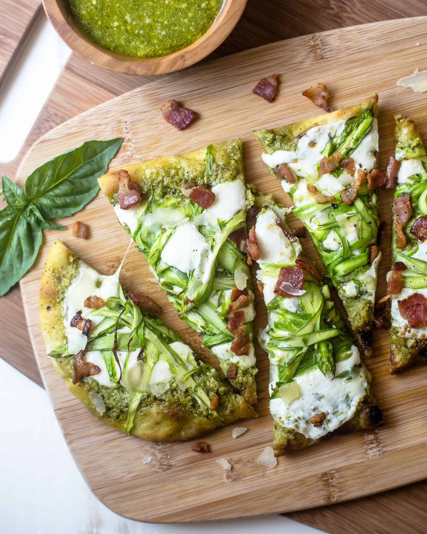Pesto Flatbread with Shaved Asparagus and Bacon, sliced on a wooden cutting board