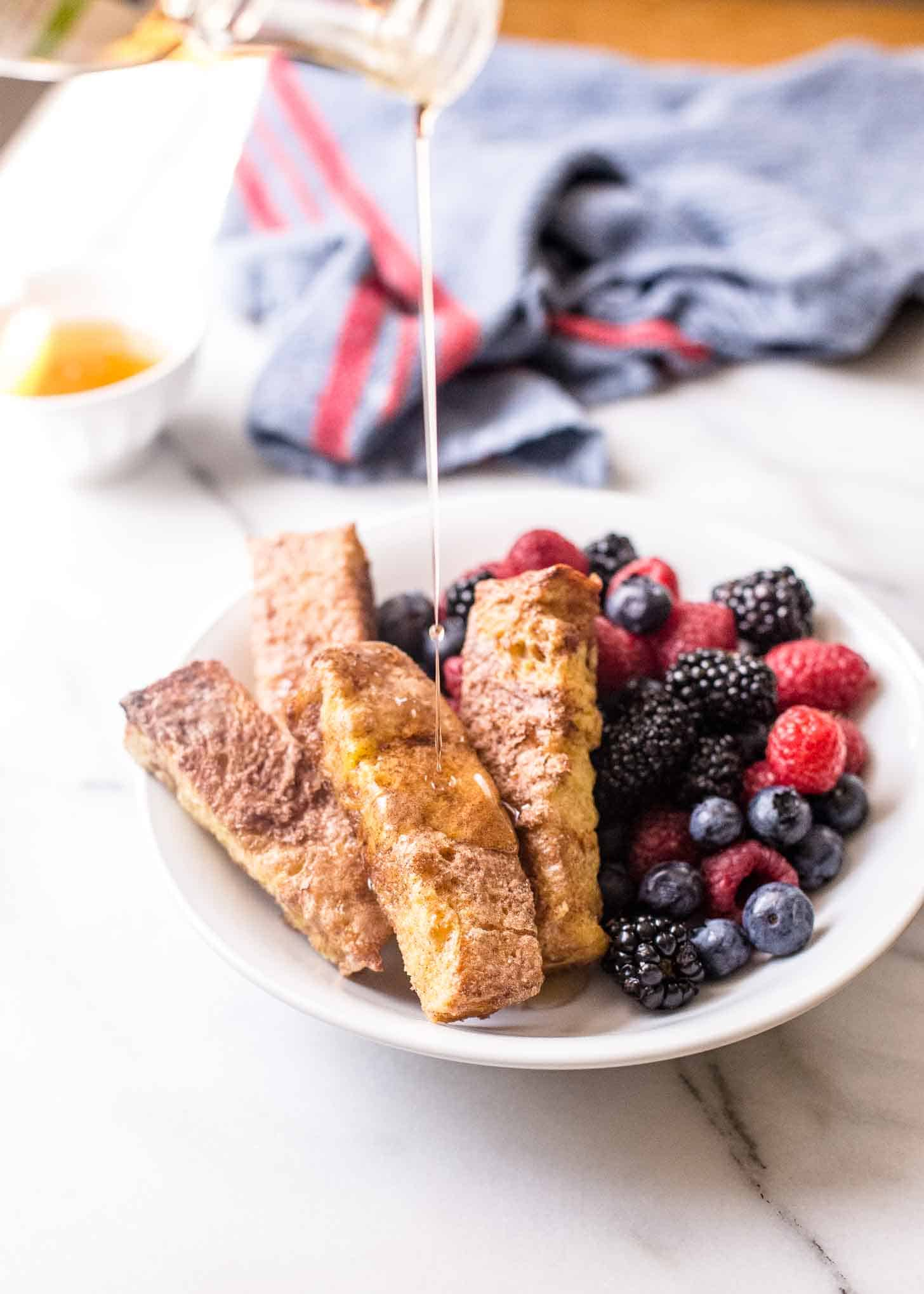 drizzling syrup on french toast sticks with berries in a white bowl