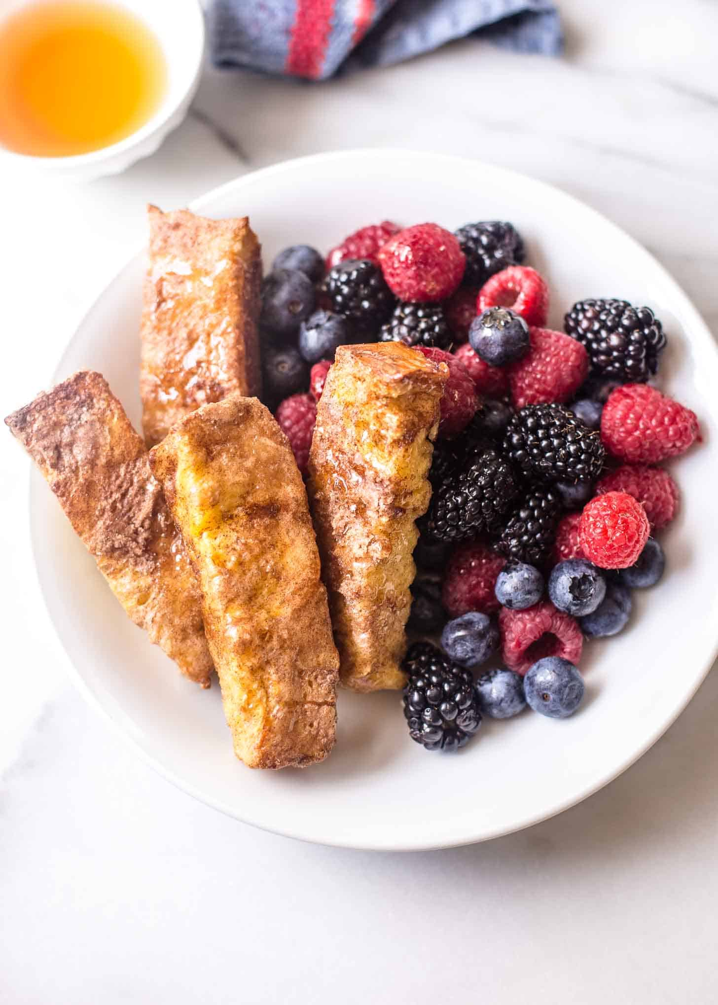 Baked Cinnamon French Toast Sticks with berries on a white plate