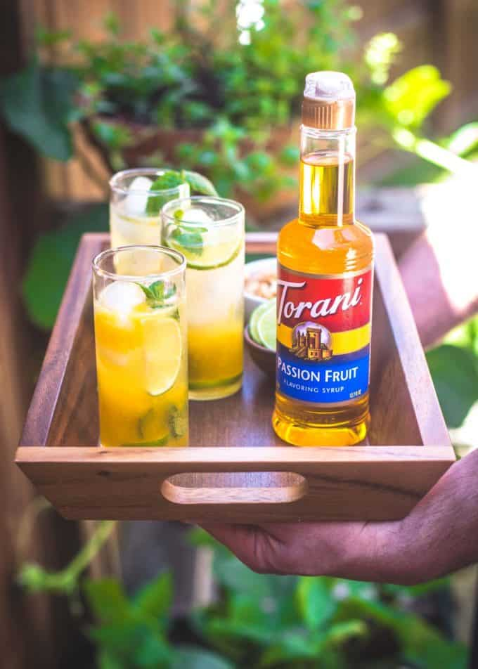 2 hands holding Passion Fruit Mojitos on a tray