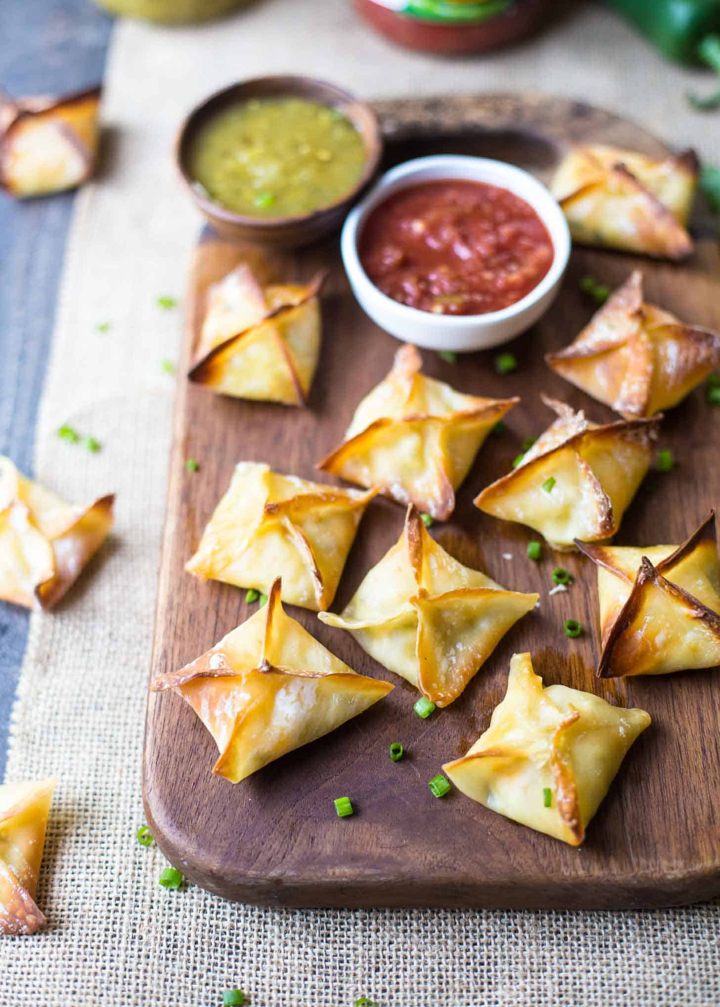 Baked Cheesy Chicken Wontons on a wooden tray with red and green salsa
