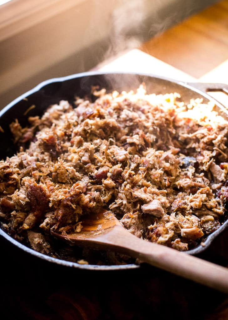 Crispy pork carnitas in a cast iron pan