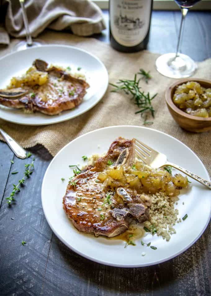 Herb Marinated Pork Chops with Apple Chutney on white plates