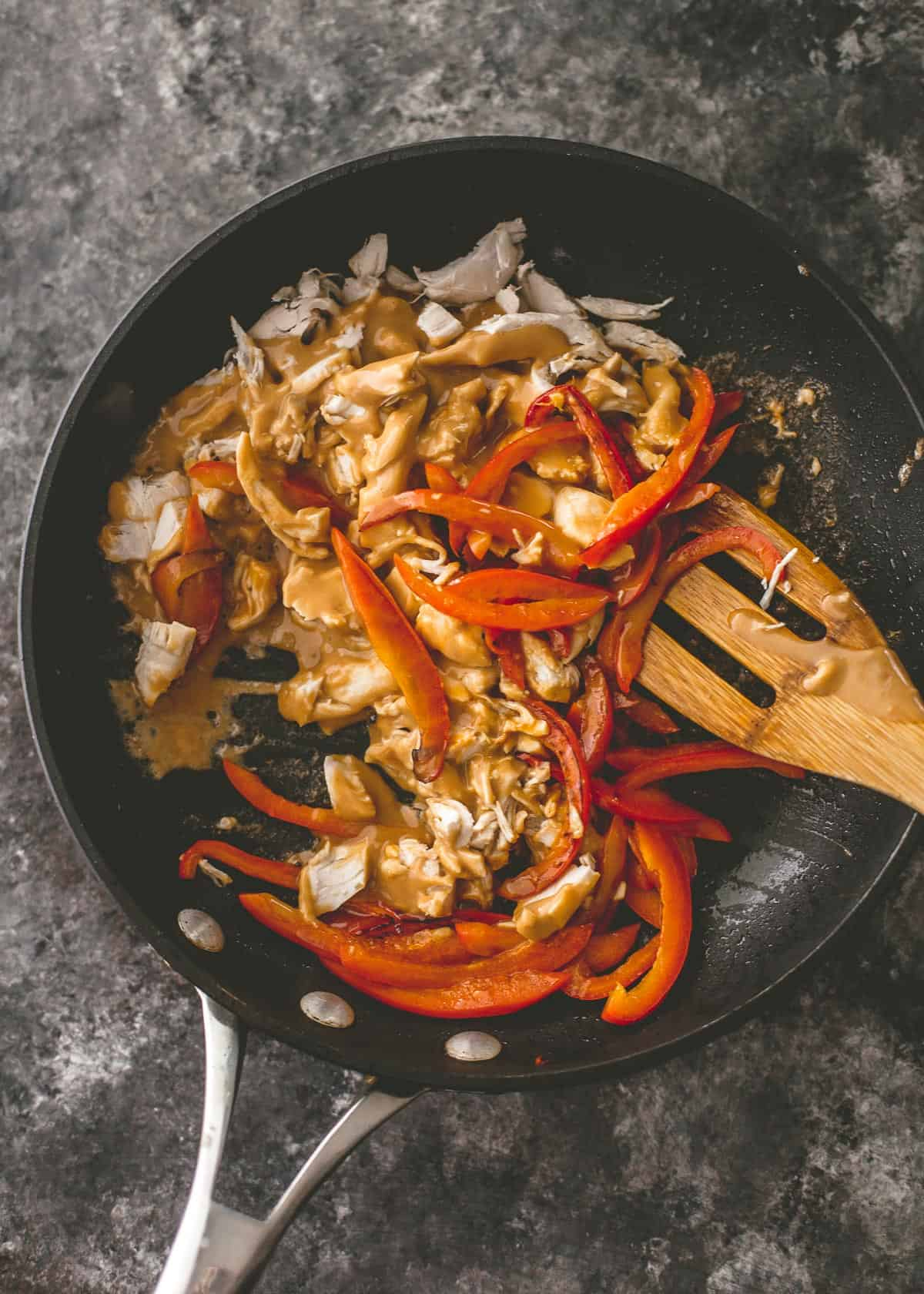 stirring peppers and chicken in a cast iron skillet