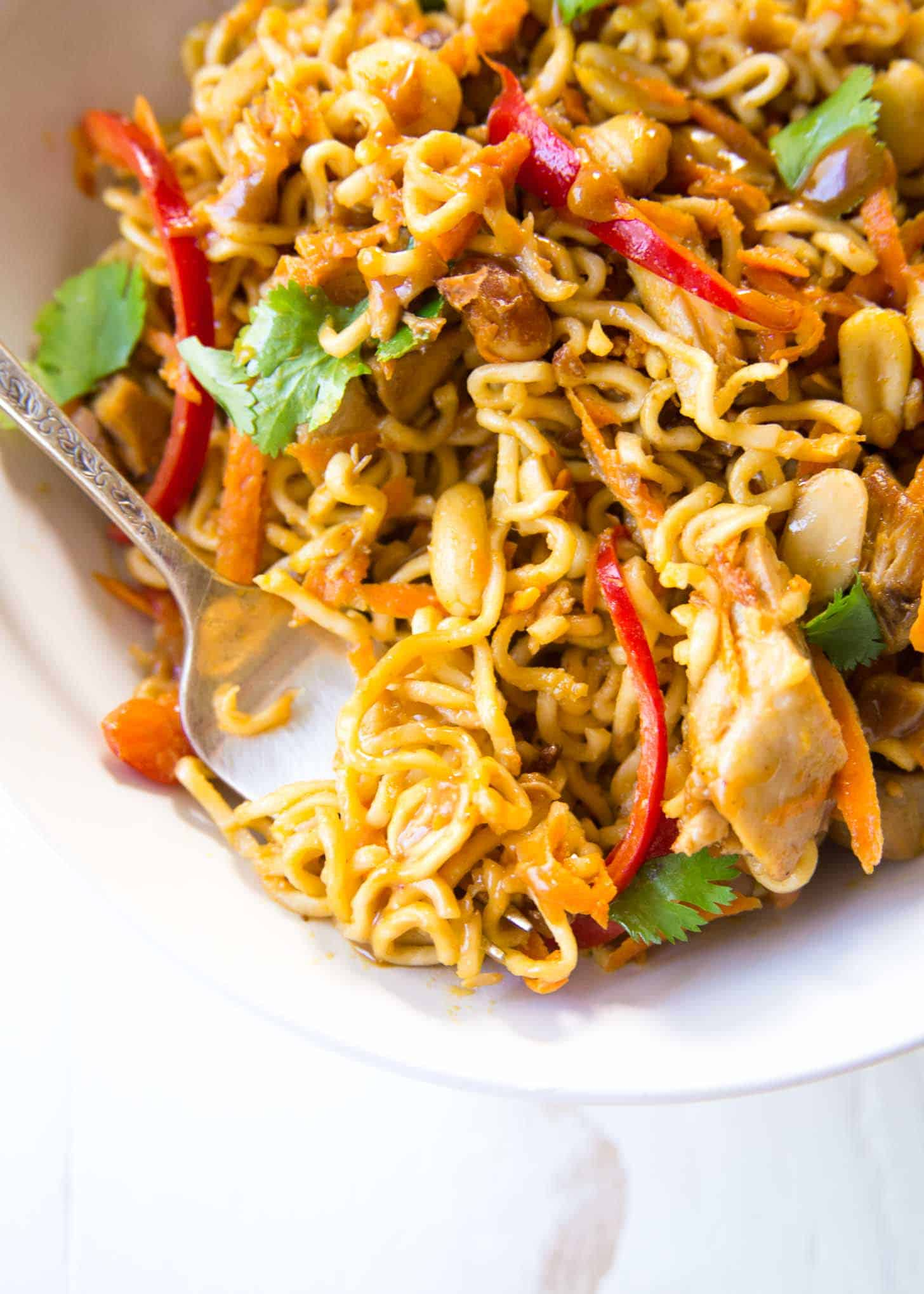 Thai Chicken Peanut Noodles with a in a white bowl with a fork