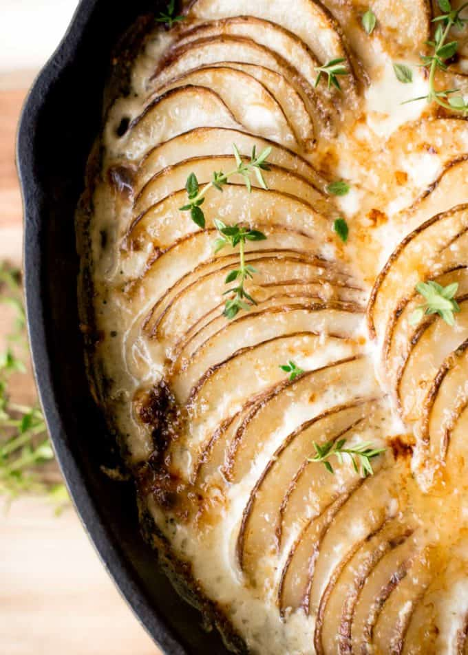 Creamy Au Gratin Potatoes with Kale and Gruyere in a cast iron skillet