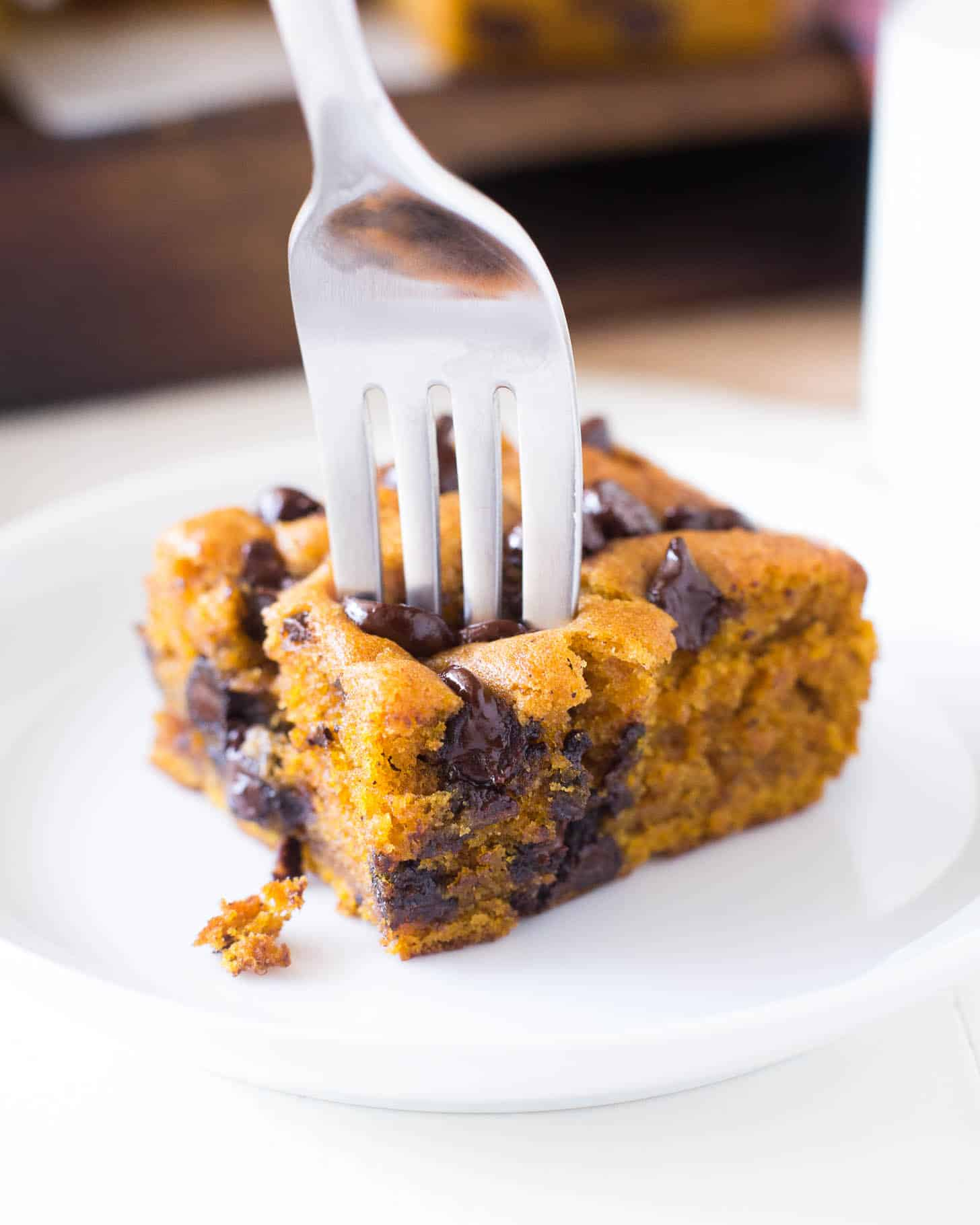a piece of pumpkin snack cake on a white plate with a fork