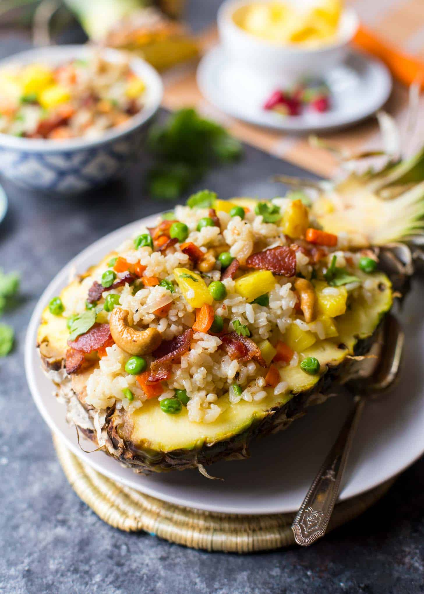 Pineapple Fried Rice served in a half pineapple on a white plate