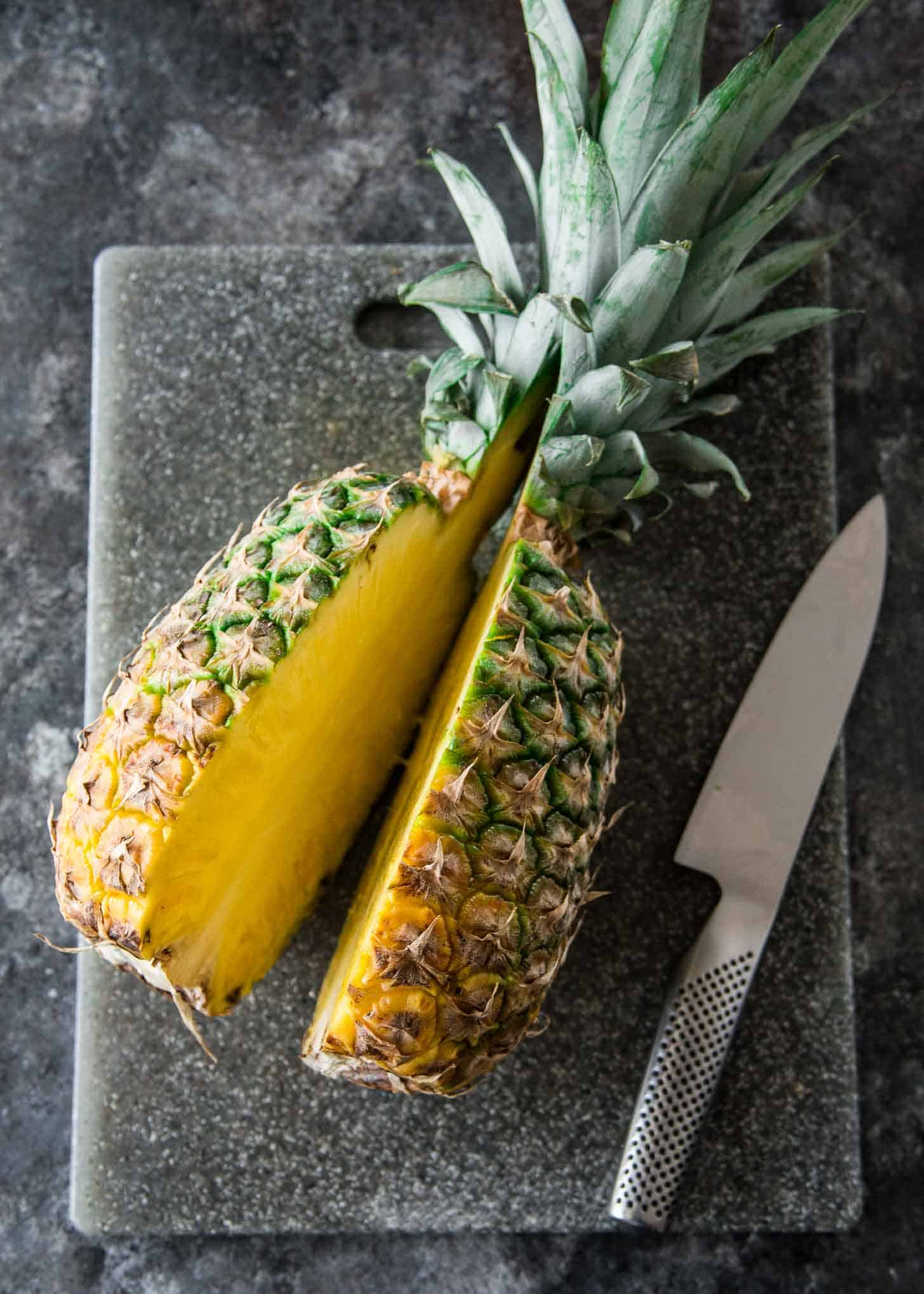 slicing a pineapple in half