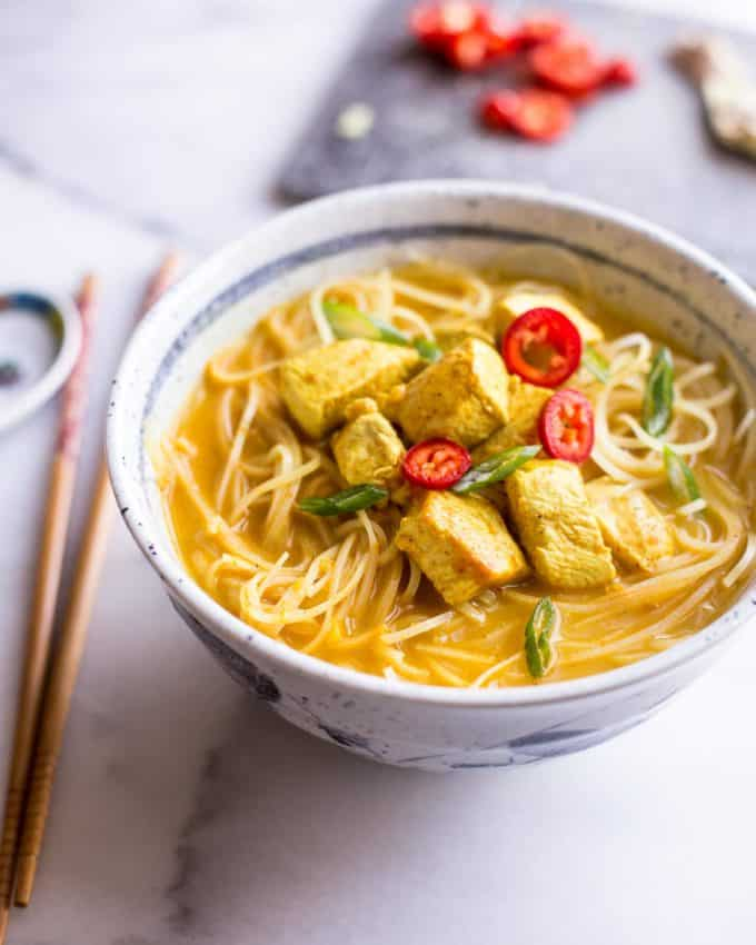 Thai Curry Noodle Soup with Chicken in a white bowl