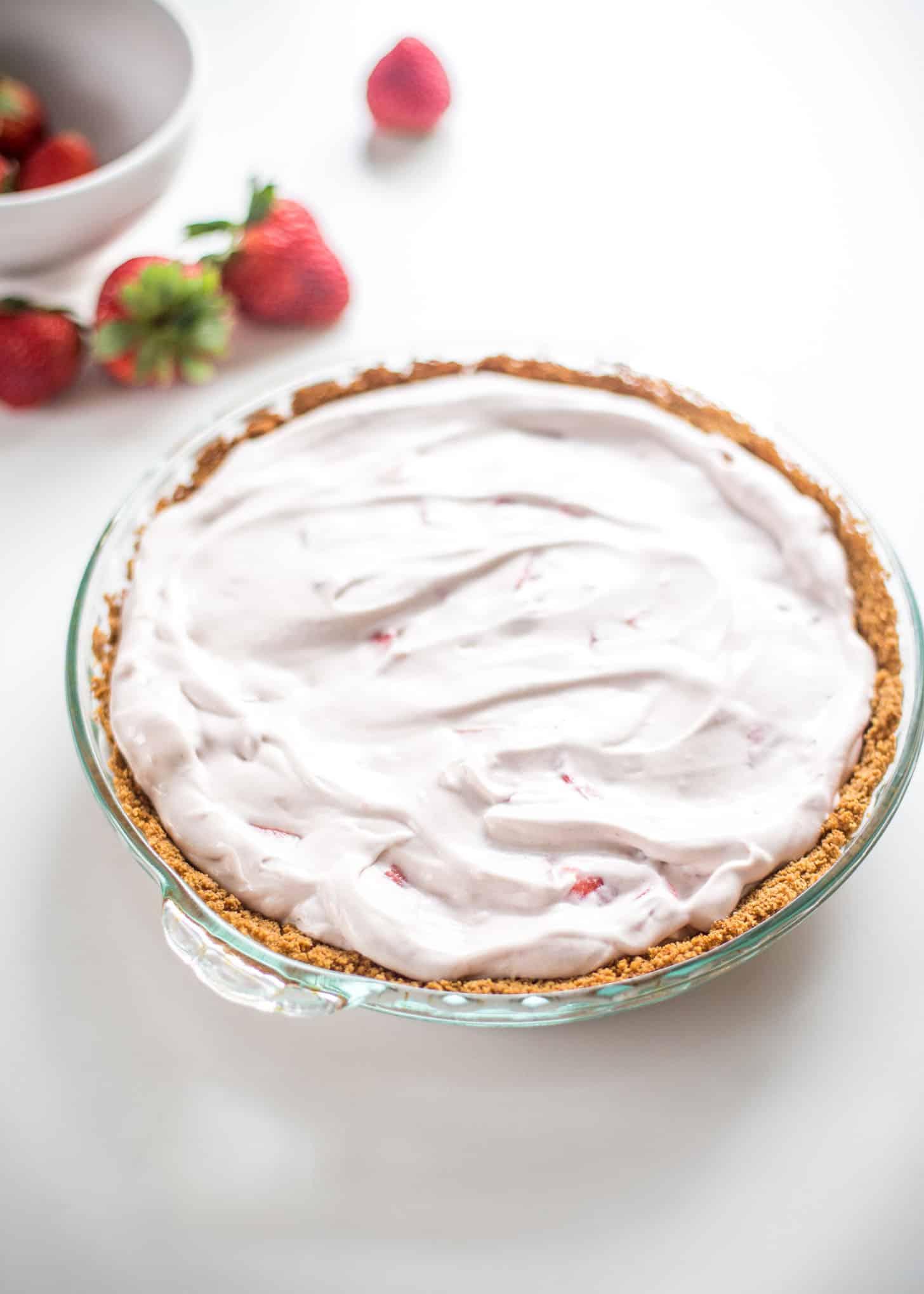 a strawberry cream pie in a clear pie dish