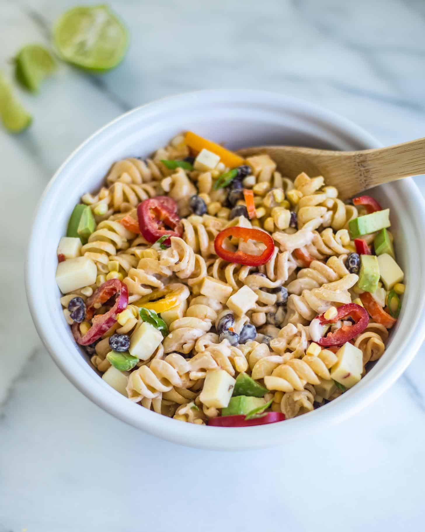 stirring pasta salad in a white bowl