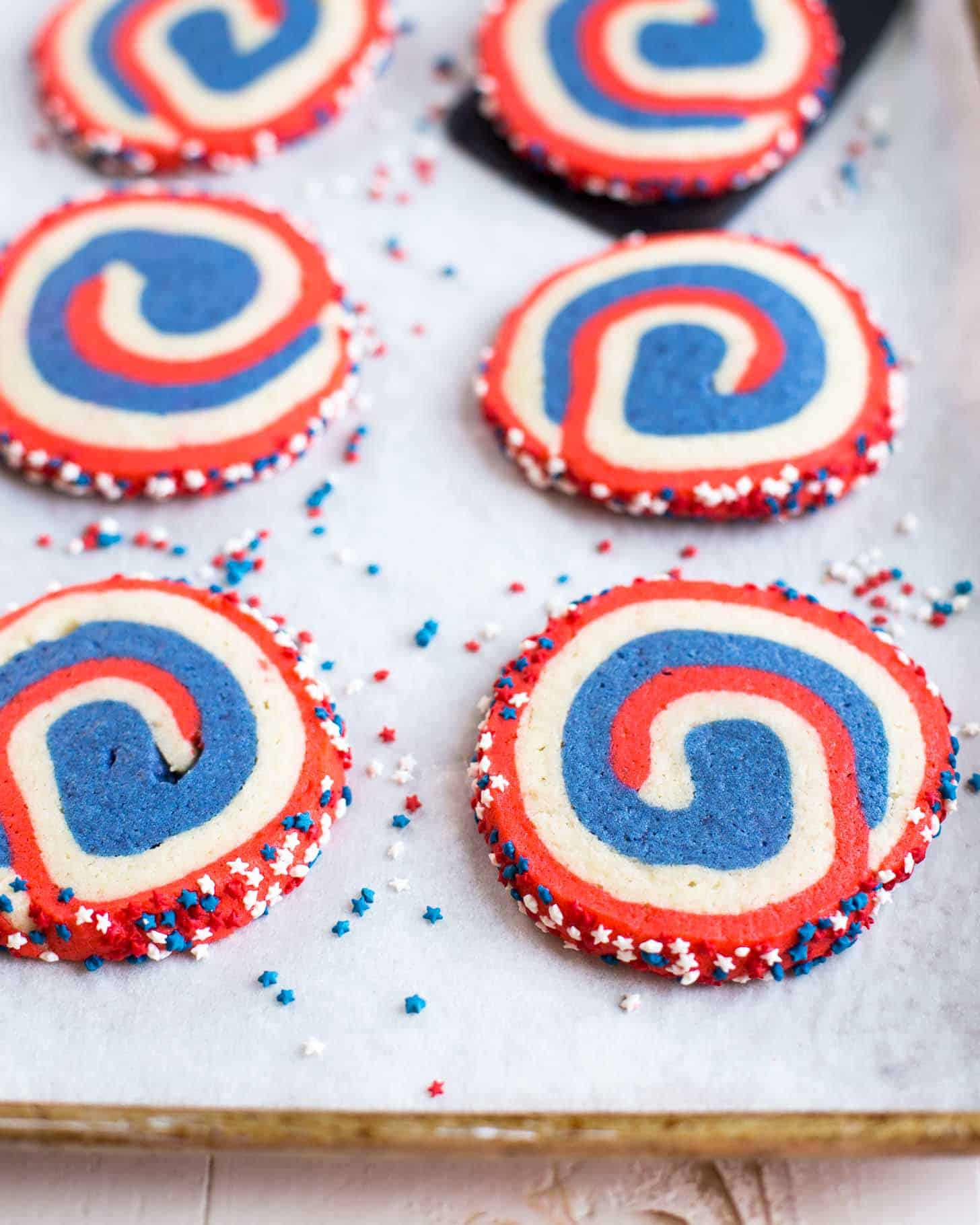 sliced pinwheel cookies on a parchment lined sheet pan