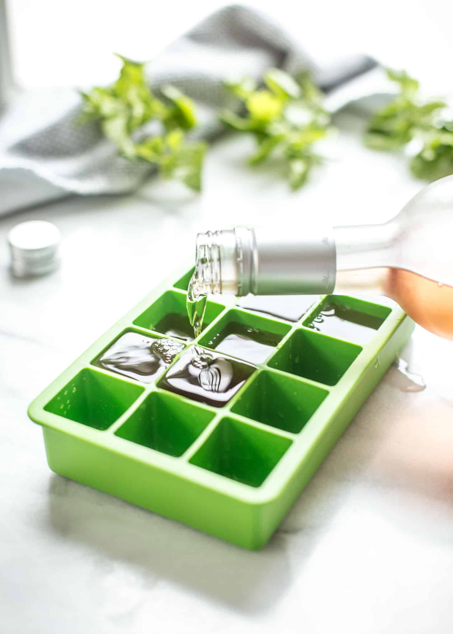 pouring white wine into ice cube trays