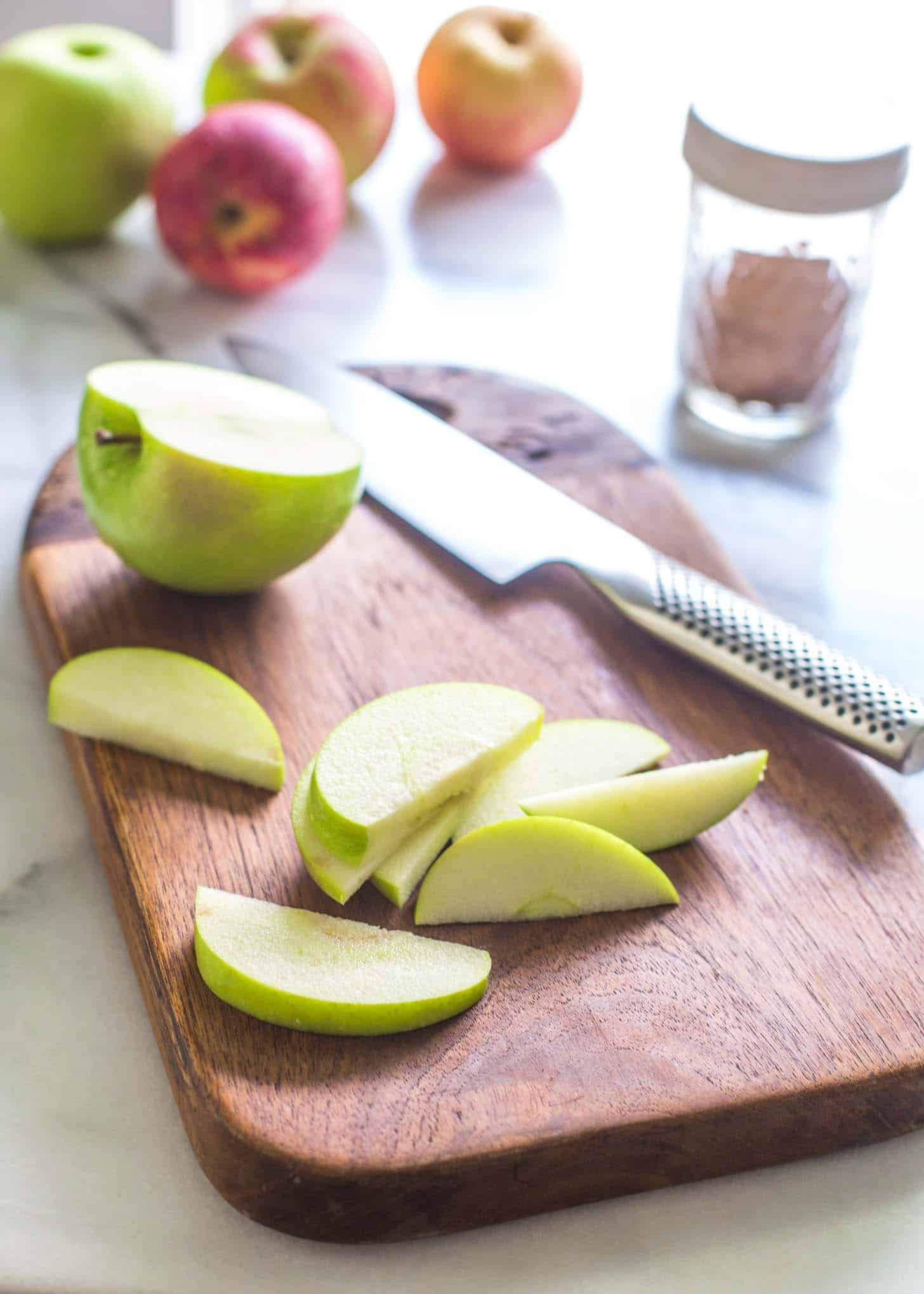 a sliced green apple on a wooden cutting board
