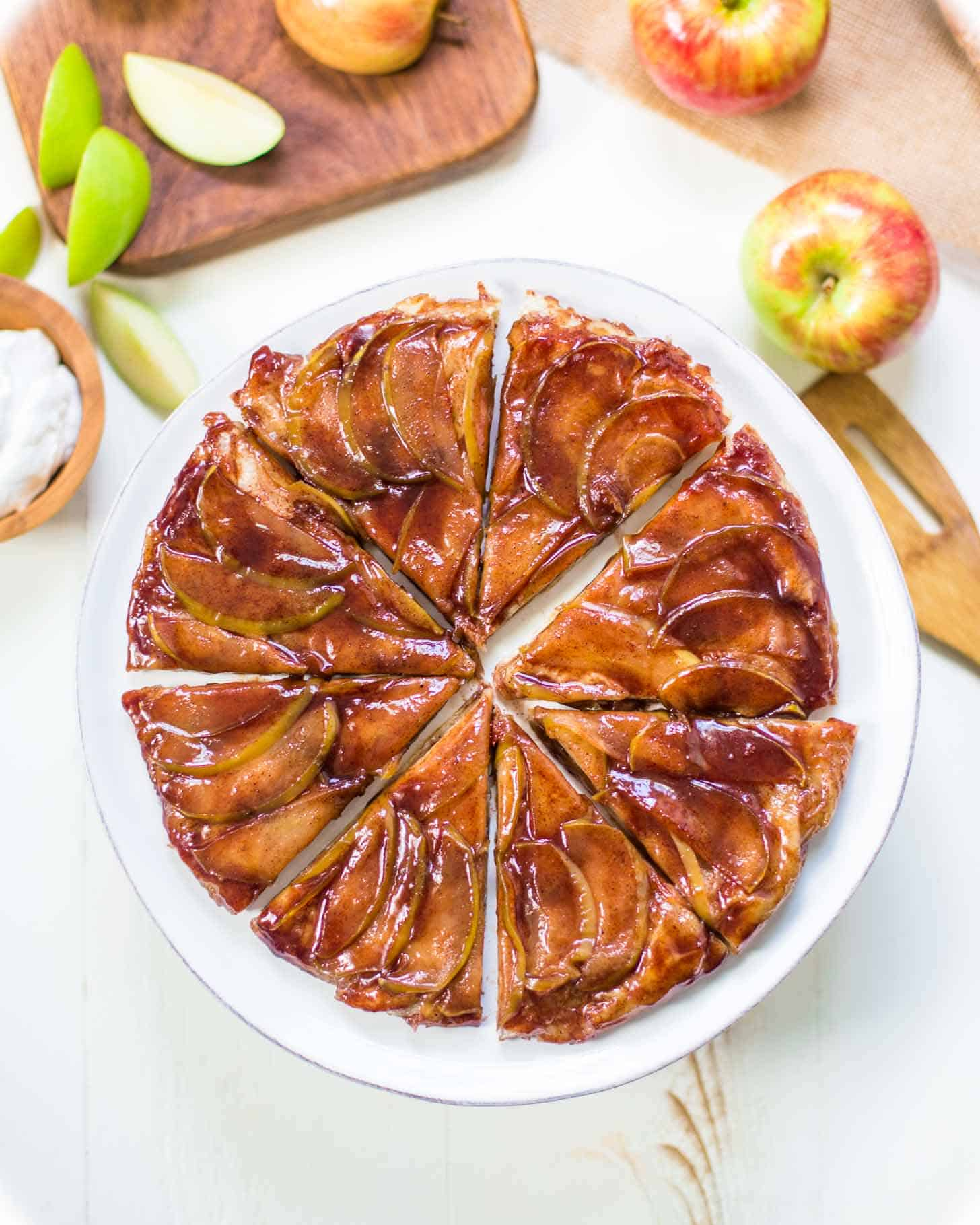 apple tart, cut into slices, on a white plate