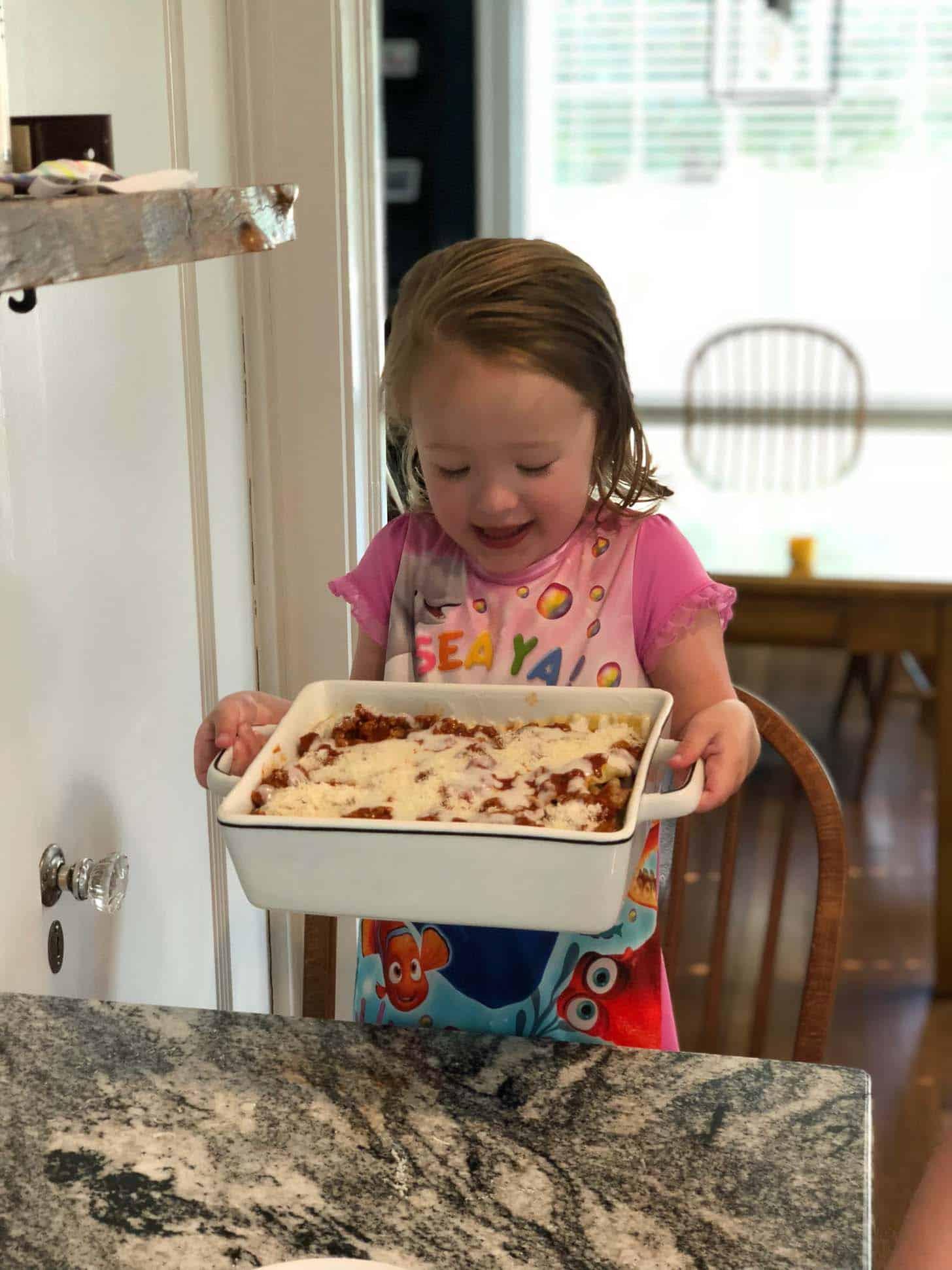 little girl holding lasagna