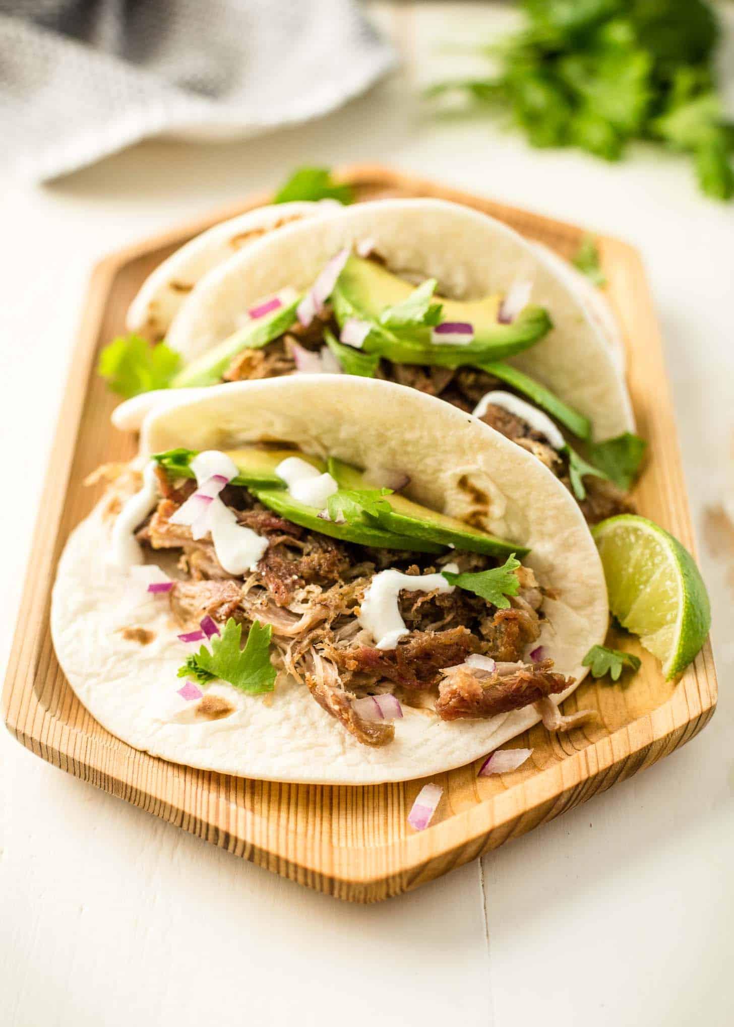 pork carnitas tacos on a wooden tray