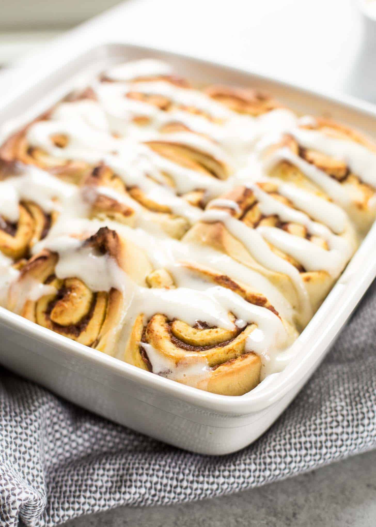 cooked cinnamon rolls in a white baking dish
