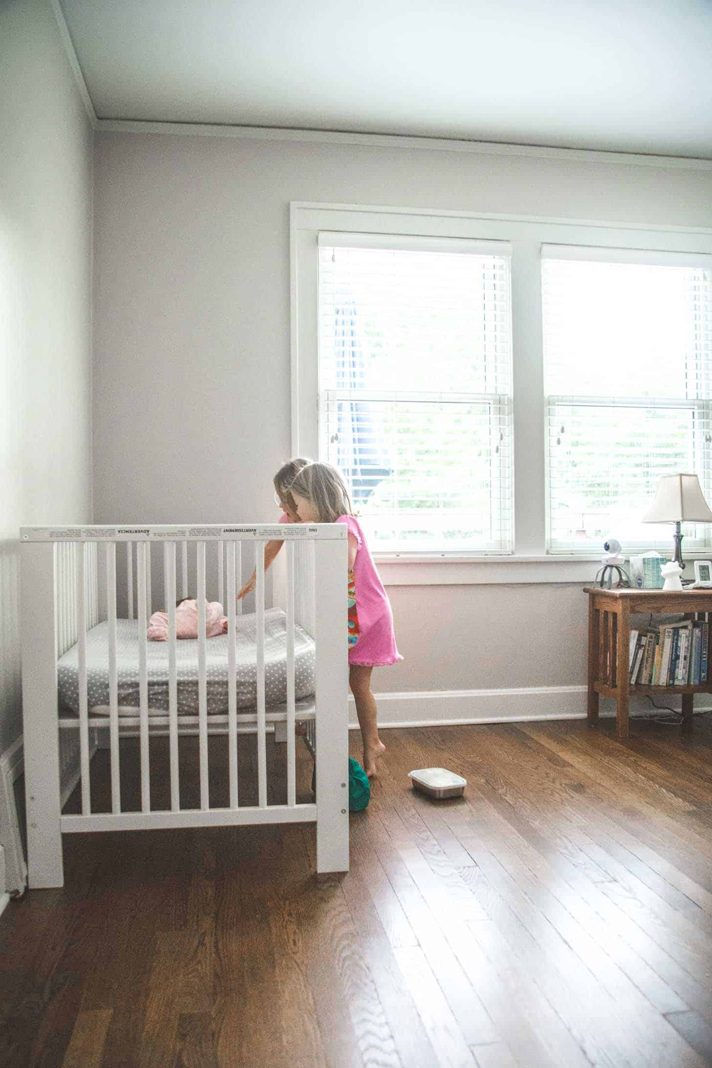two little girls looking at a baby in a crib