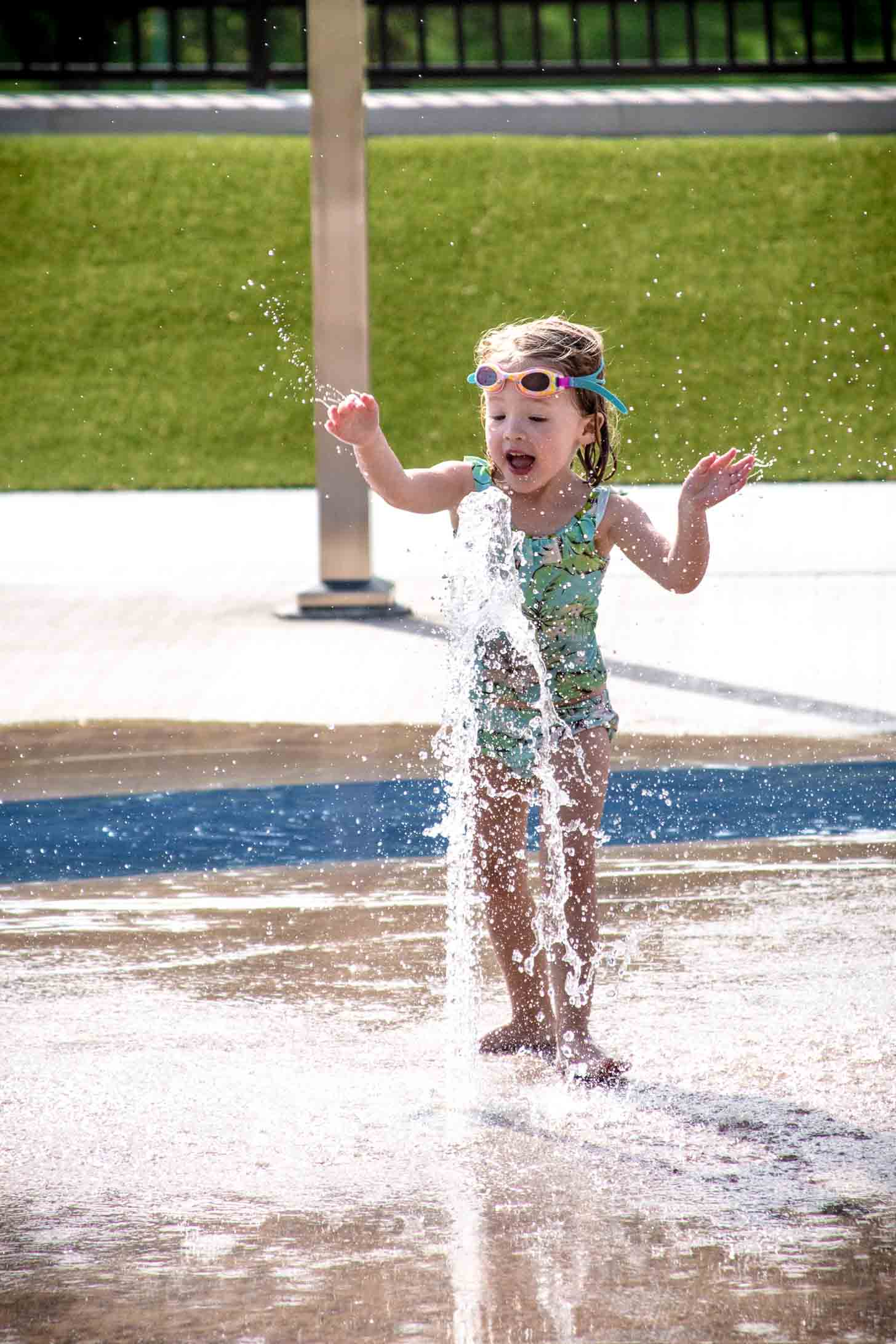 a little girl in a bathing suit and swim goggles playing in the water