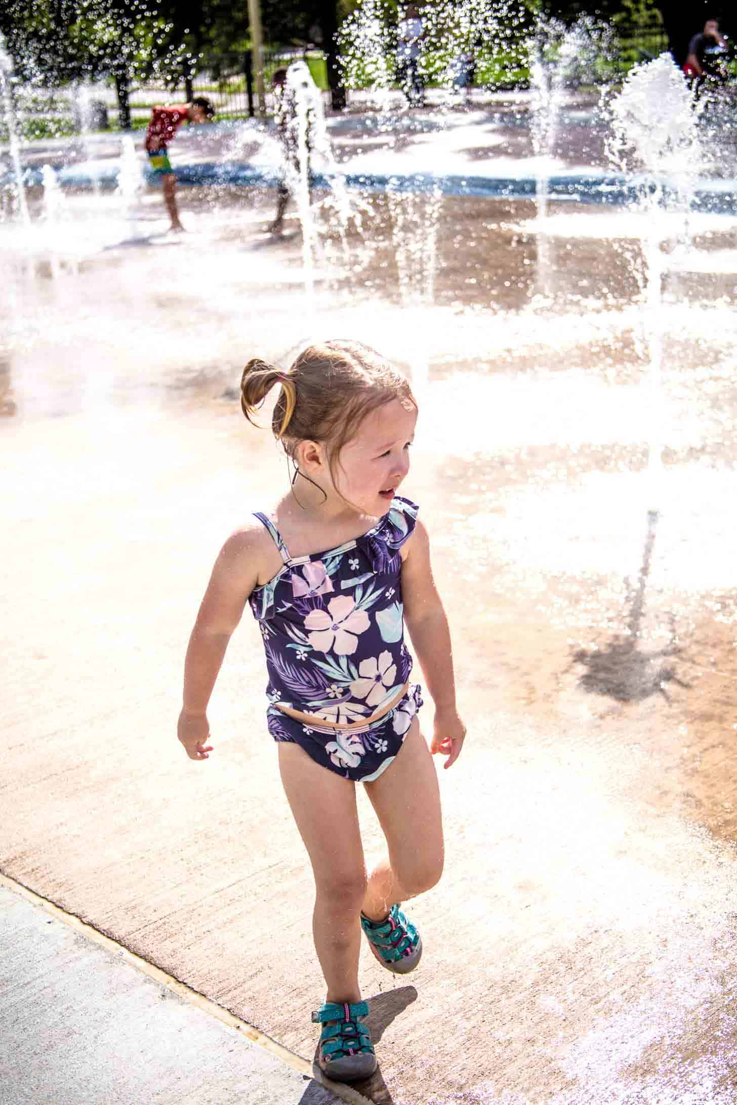 a little girl in a bathing suit playing in the water