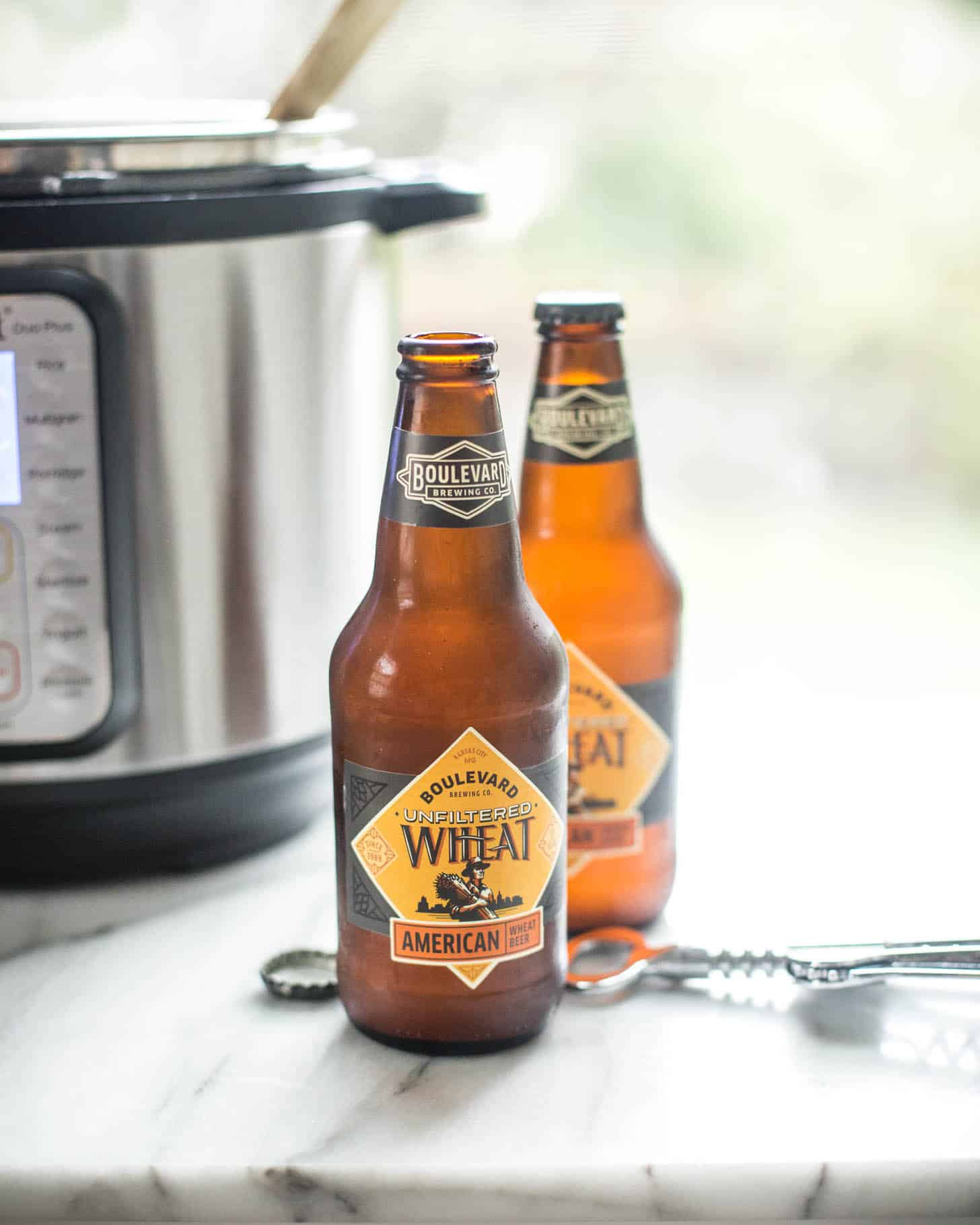 two bottles of beer next to an instant pot