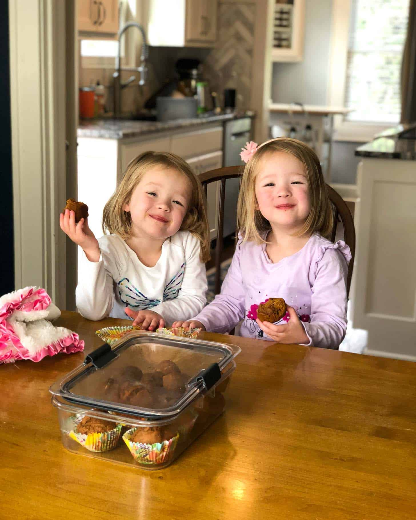 two little girls at a table eating muffins