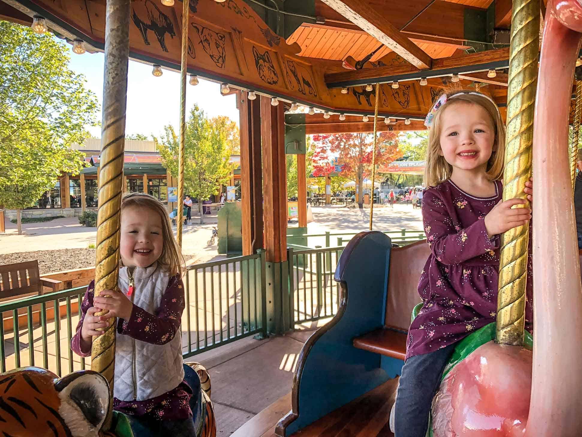 little girls riding a carousel