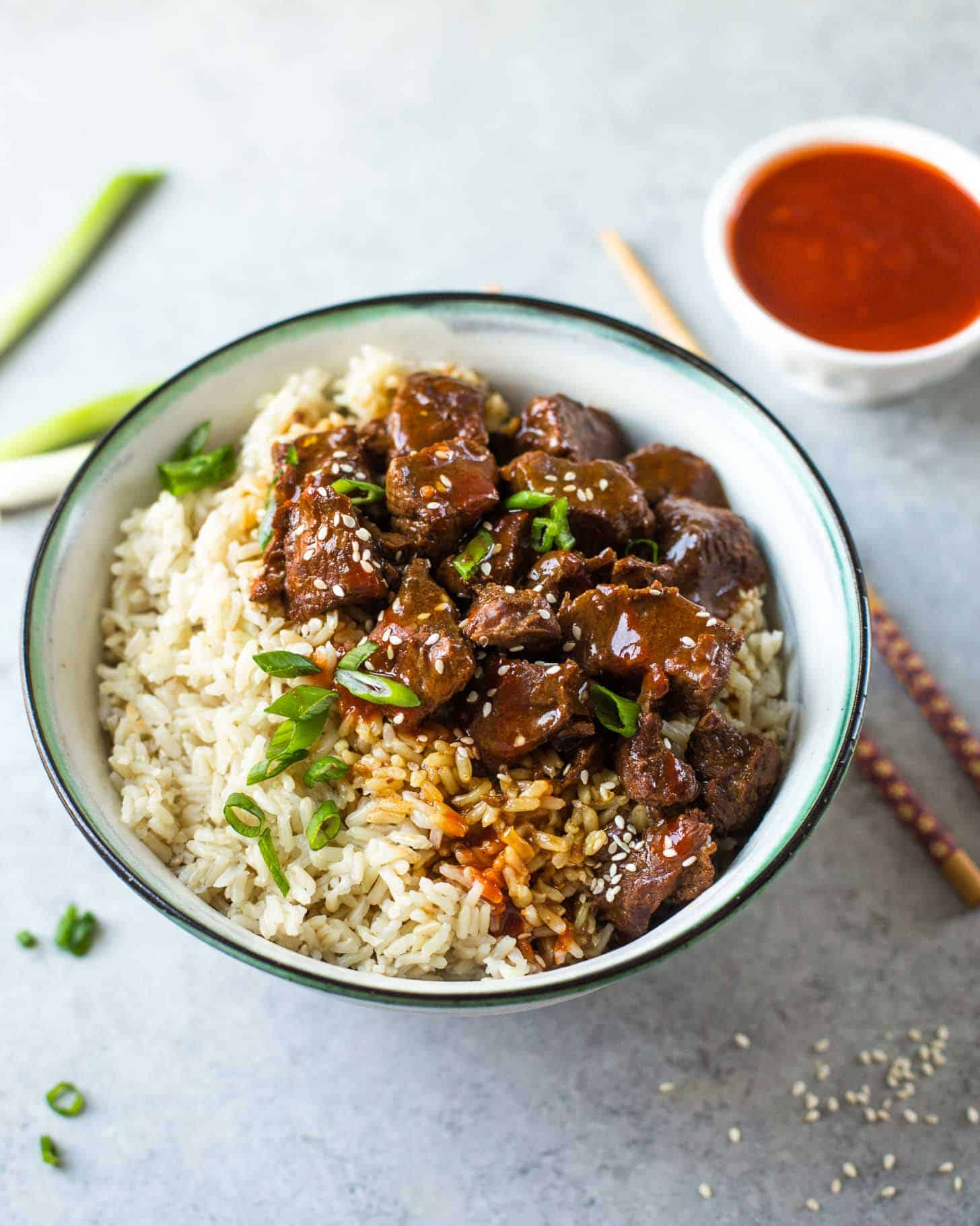 beef and brown rice in a white bowl