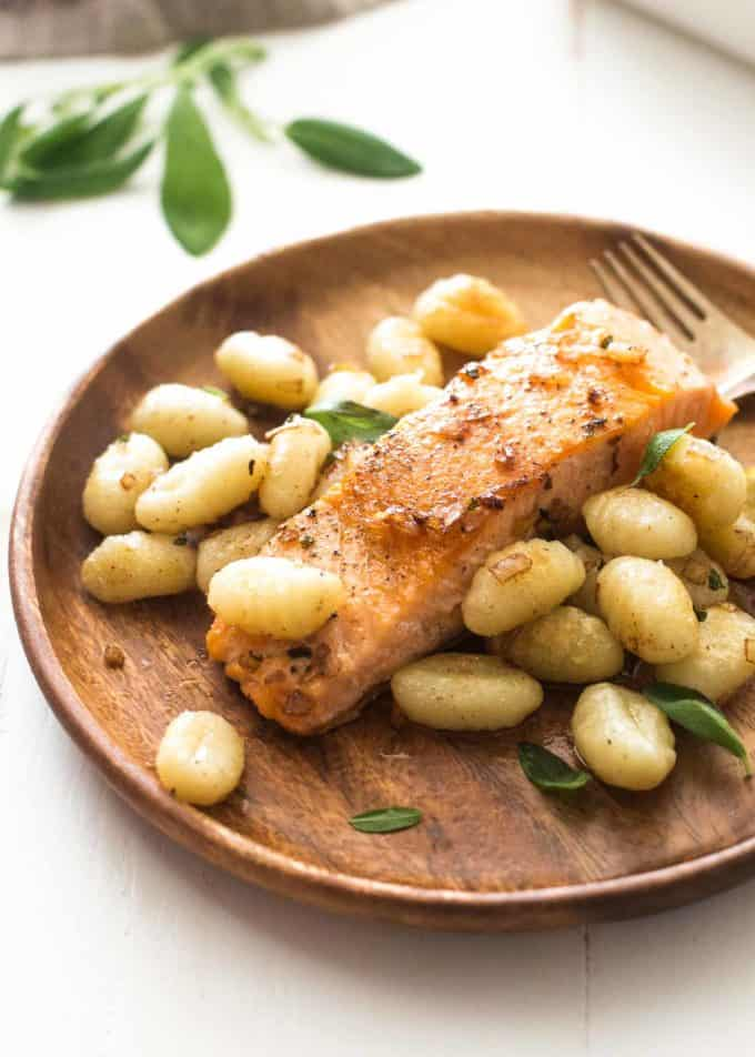 salmon and gnocchi on a wooden plate