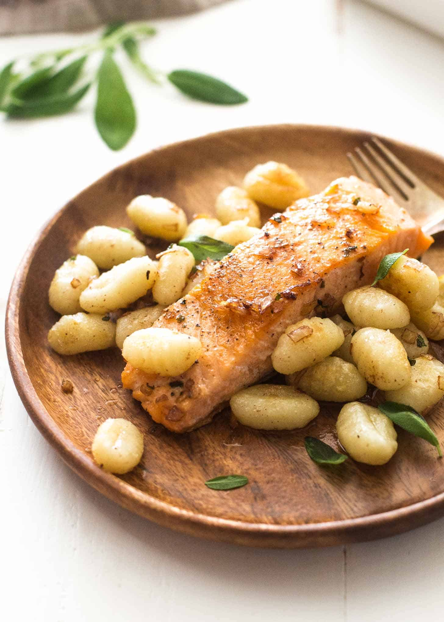 Pan Seared Salmon and Gnocchi with Sage Butter Sauce on a wooden plate