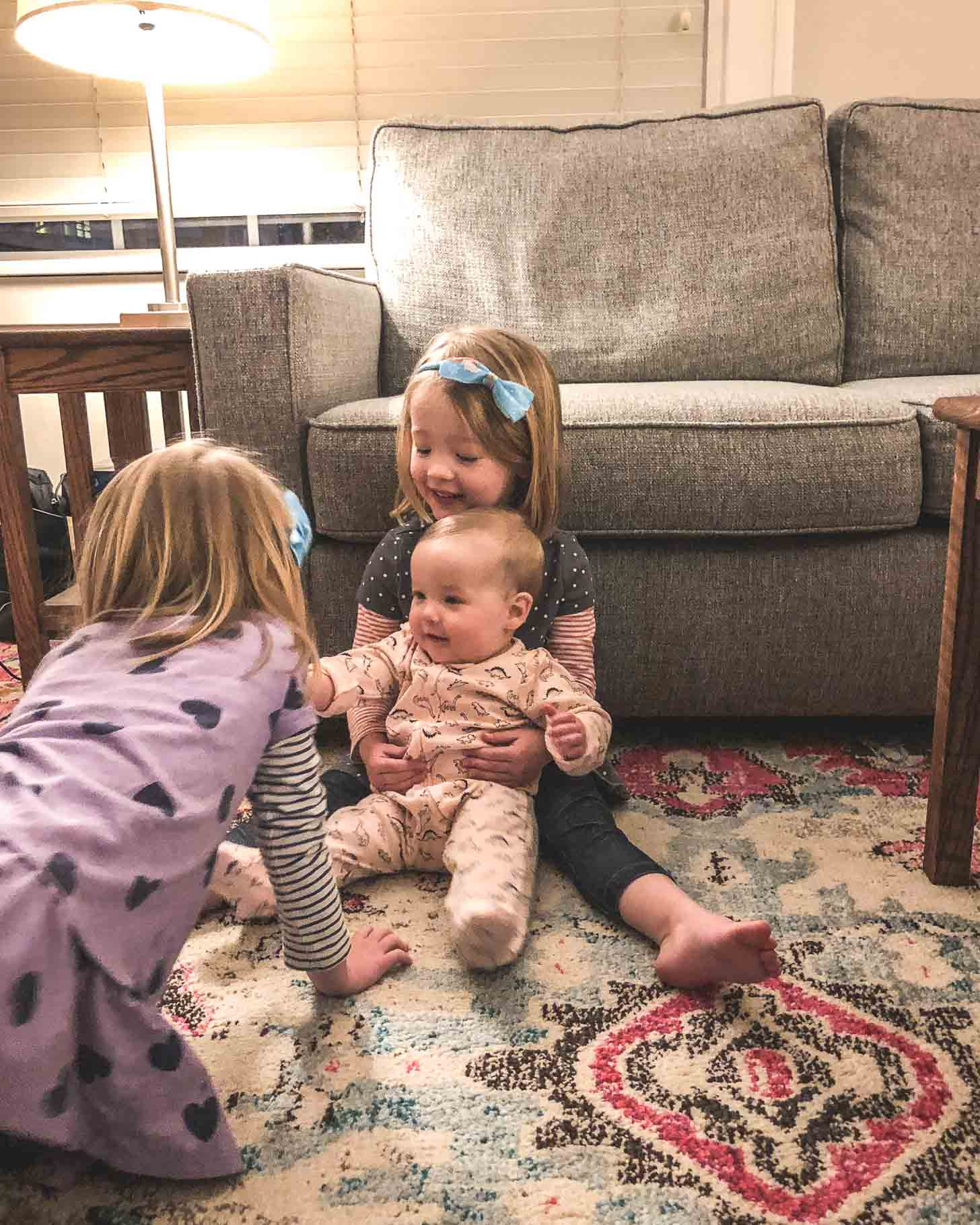 Two girls and a baby on a rug