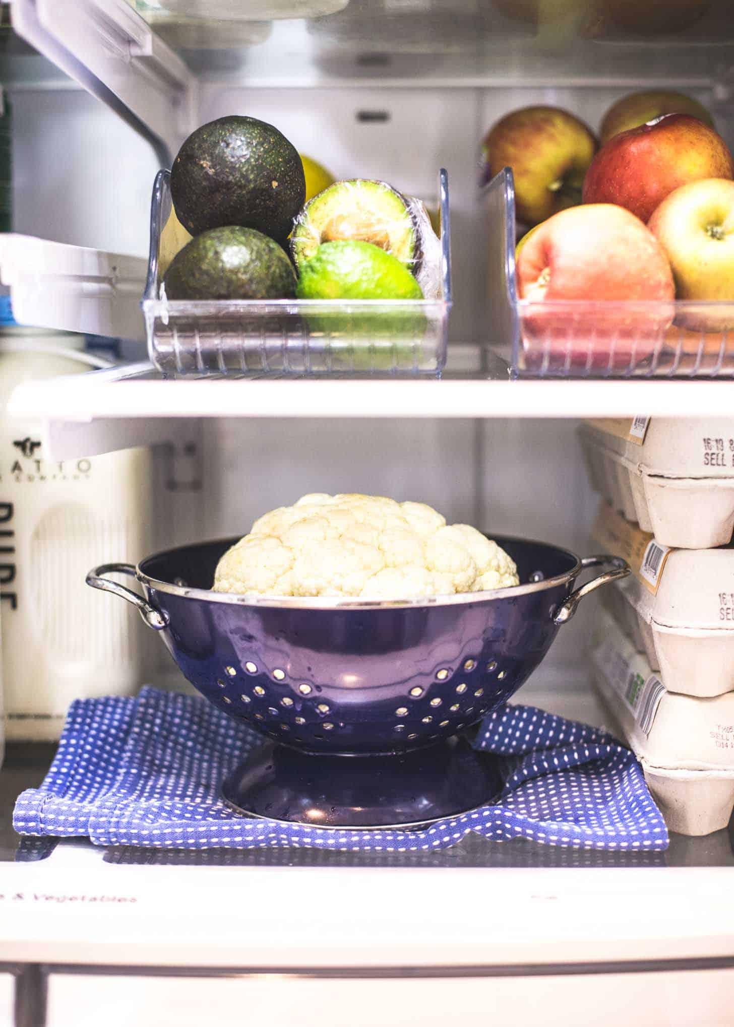 raw cauliflower in a colander in the fridge