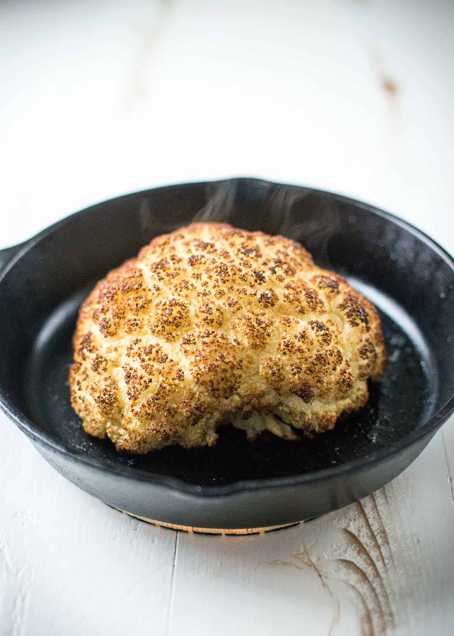 Whole Roasted Cauliflower in a cast iron skillet